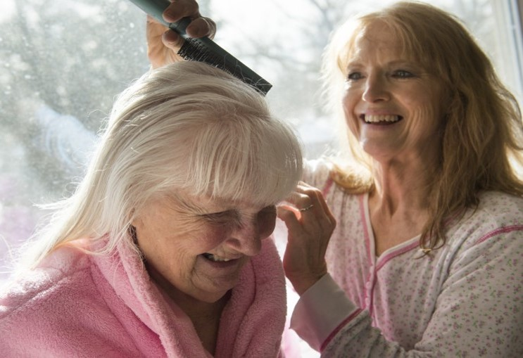 A woman brushes her elderly mother's hair.