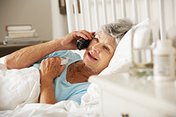 Sick Senior Woman In Bed At Home Talking On Phone