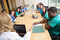 A group of doctors, nurses, and other clinicians meet to discuss patient care.