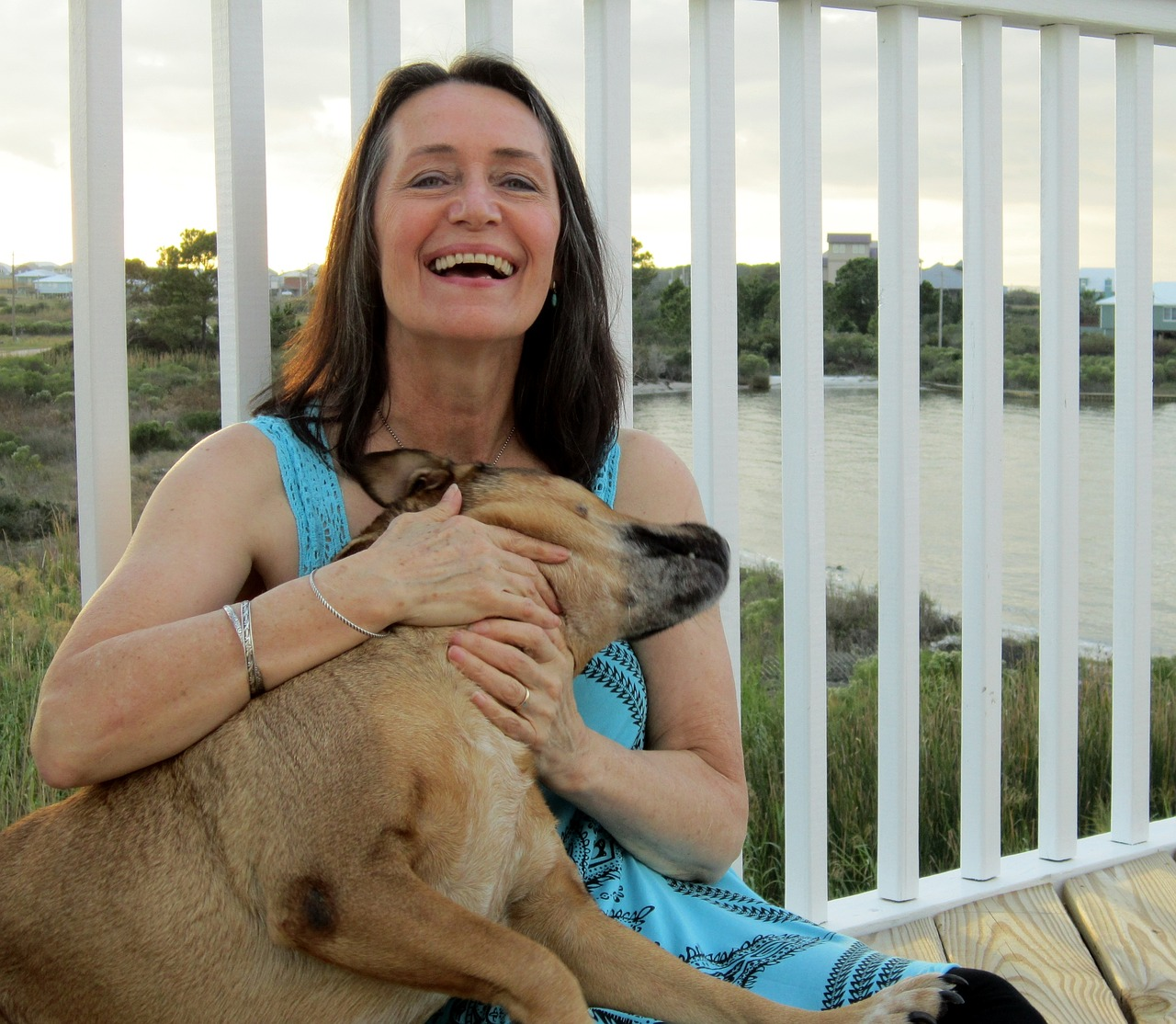 Mature woman sitting and holding a dog, 5 Things You May Not Know About Psoriasis