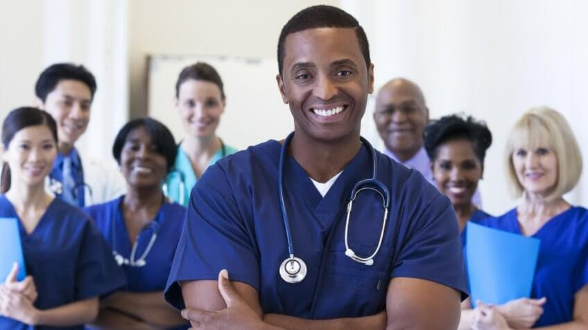 group of smiling young health care workers in scrub tops
