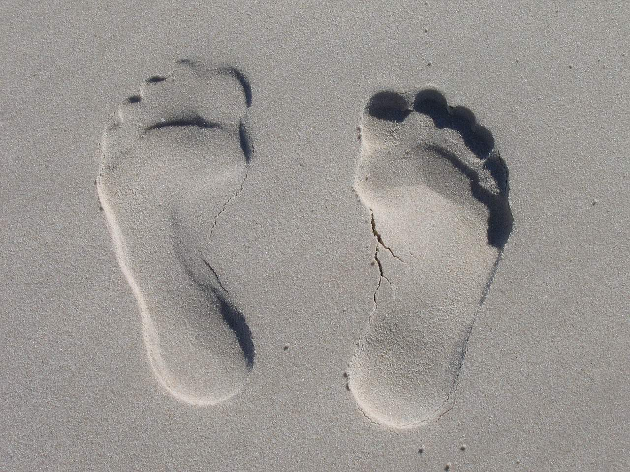 imprints of human feet in sand